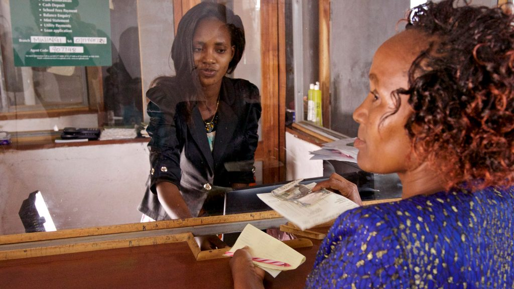 Micro borrower who is making an installment payment on her loans. The Bank has a repayment rate of approx. 97%